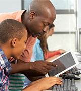 Teacher who is taking Flipping Classroom Instruction Professional Program courses instructing students with a mobile tablet